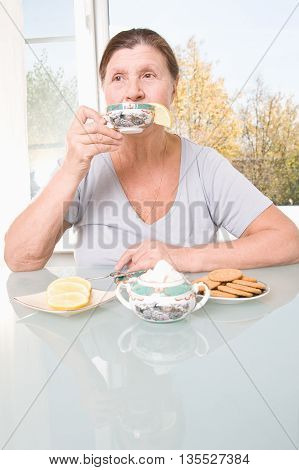 Thoughtful elderly woman drinks tea sitting at the table. Studio photography in bright tones.