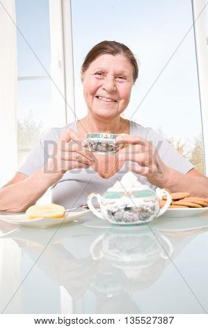 Smiling elderly woman drinks tea sitting at the table. Studio photography in bright tones.