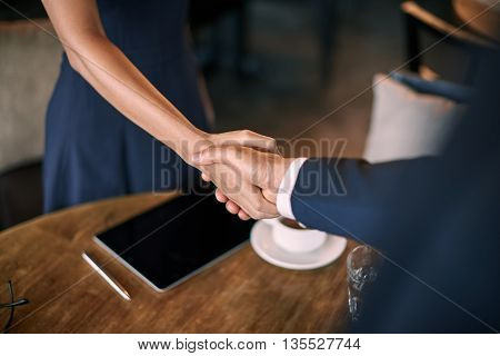 Close-up of handshake of colleagues meeting in cafe