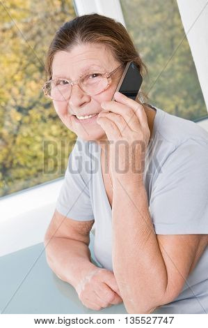 Happy elderly woman sitting at a table and talking on a cell phone.
