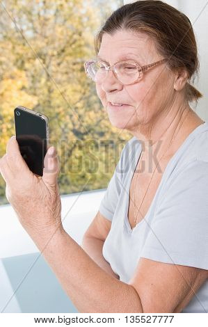 Smiling elderly woman looking at the mobile phone screen.