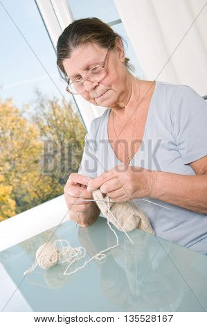 An elderly woman knit woolen socks. Studio photography.