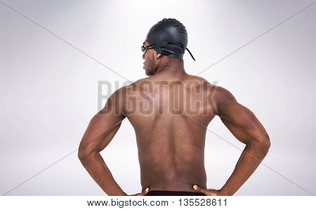 Rear view of swimmer on white background against grey background