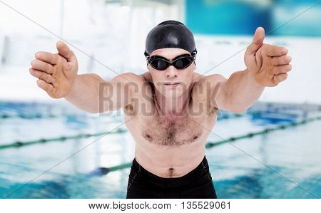 Swimmer preparing to dive against view of a swimming pool