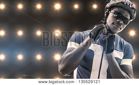 Composite image of athletic man putting his cycling helmet against spotlight