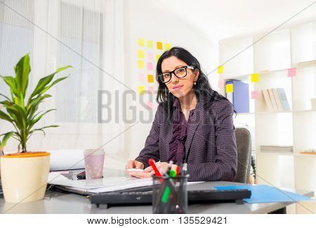 Young businesswoman sitting at workplace holding the phone in her hand