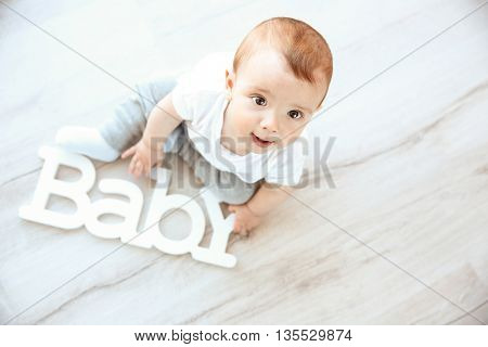 Cute baby boy with wooden word Baby