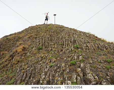 Tourist On Sharp Basalt  Peak Of Volcano  Formation