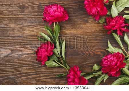 Round made from crimson peonies on the wooden background