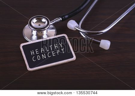 Medical Concept-Healthy CONCEPT words written on label tag with Stethoscope on wood background