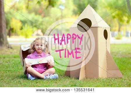 Text Happy Time and little girl in carton helmet sitting near carton rocket in the park