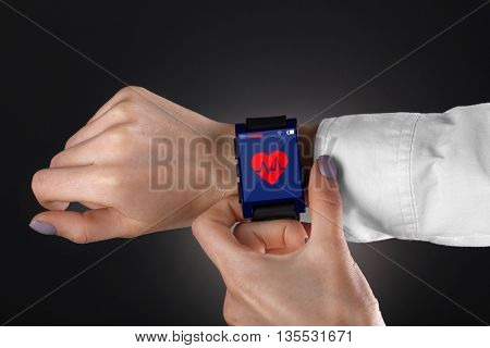 Hands with heart icon on smart watch on black background
