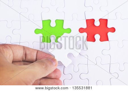 Missing jigsaw puzzle piece with lgreen and red business concept for completing the final puzzle piece