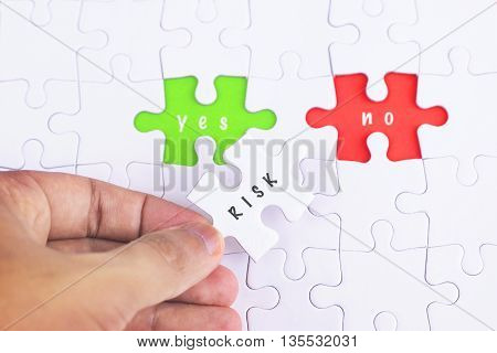 Business Concept - Female hand and missing puzzle with RISK YES and no WORD