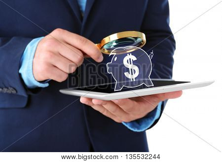 Businessman holding magnifying glass and digital tablet with virtual piggy bank