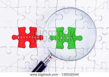 BUSINESS CONCEPT - Magnifying glass on missing puzzle with a word questionand answer
