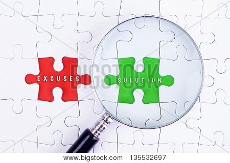 BUSINESS CONCEPT - Magnifying glass on missing puzzle with a word EXCUSES AND SOLUTION