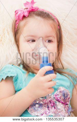 Little girl using an inhaler indoors. nebulizer