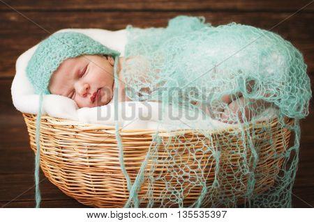 Newborn baby sleeping on a wooden background