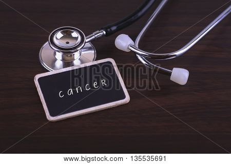 Medical Concept- cancer words written on label tag with Stethoscope on wood background