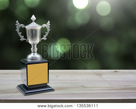 champion silver trophies on wood table with lighting victory. (business success concept)