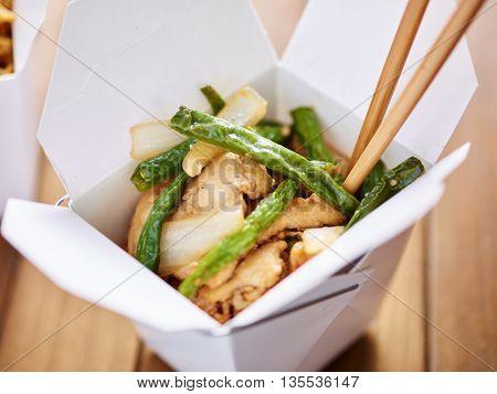 eating chinese take out from container with chopsticks