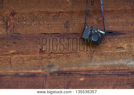 Vintage digital compact photo camera hanging on a wooden wall