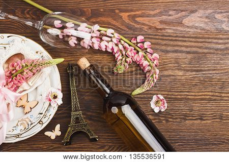 Tableware with pink lupinus silverware and decorations on the wooden background