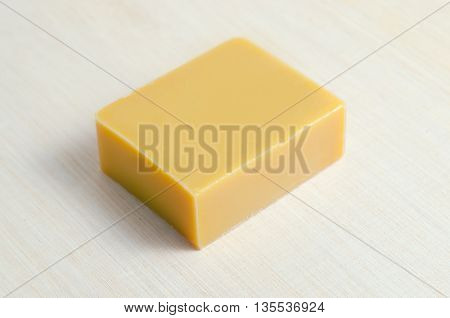 Soap bar isolated on wooden board beautiful soap bar with mango scent fulfilled with natural ingredient