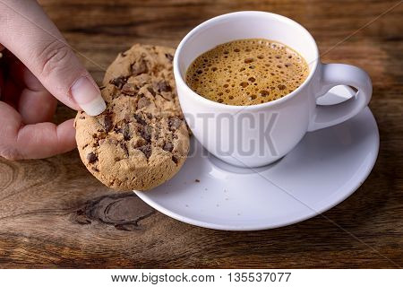 cup of coffee with chocolate cookies and female hand on wood