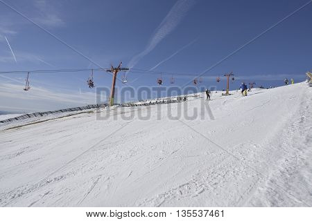 Ski slope with chairlift in the background and blue sky