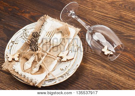 Tableware and silverware with dry decorations on the wooden background