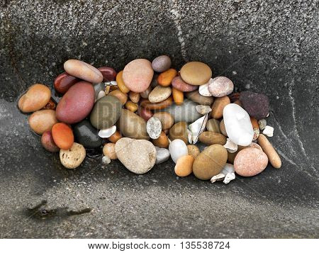 A close-up view of coloured sea polished pebbles lying in a  depression in a rock.
