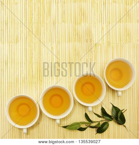 Tea cups with green leaves on Chinese background