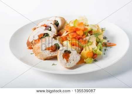 Chicken rolls with ratatouille served on a white plate