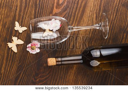 Empty wineglass and full bottle with decorations on the wooden background