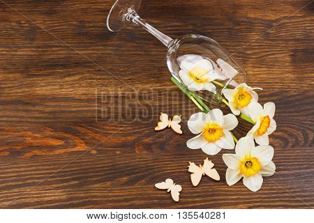 Wineglass with narcissus and decorations on the wooden background