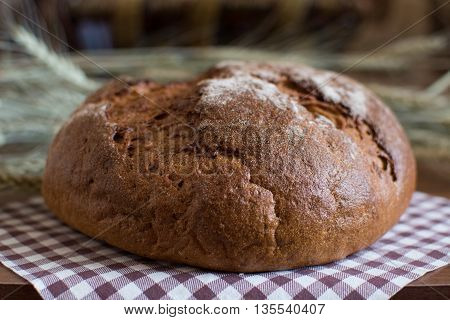 Craft round bread made from rye and wheat flour without yeast, without baking powder, not containing GMOs rests on a checkered napkin