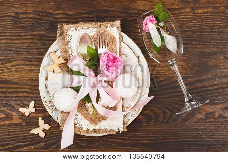 Table serving: tableware and silverware with decorations. Light pink roses marshmallows and wooden butterflies on the wooden background