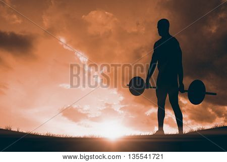 Bodybuilder lifting heavy barbell weights against landscape with sunset