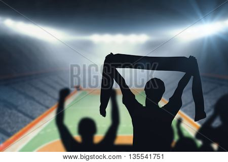 Silhouettes of football supporters against handball field indoor
