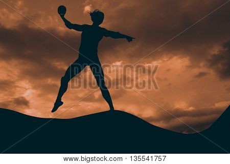 Female athlete throwing handball against clouds