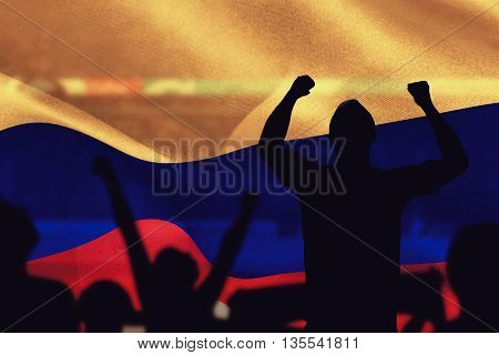 Silhouettes of football supporters against composite image of