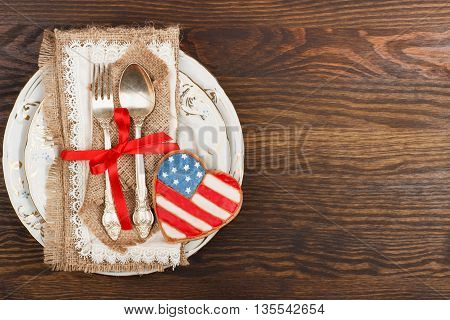 Tableware and heart shaped cookies with American patriotic colors on the wooden background