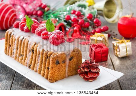 Sweet Christmas fruit cake with raspberries on rustic wood background