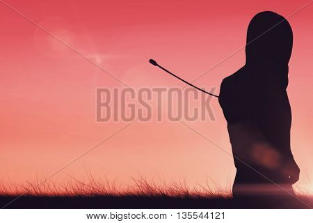Man wearing fencing suit practicing with sword against sunset