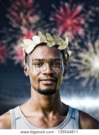 Portrait of victorious sportsman with crown of laurels against fireworks exploding over football stadium