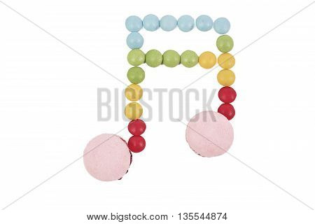 multicolored macaron chocolate candy musical note on white background