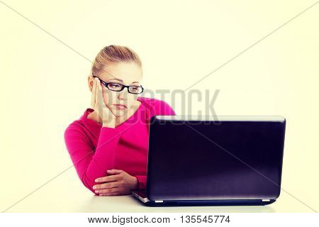 Bored, sad woman sitting in front of laptop.