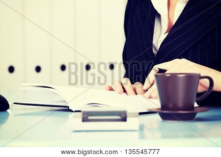 Business woman is writting in notebook.